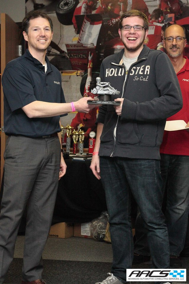 A CCS Student accepts the Tail Light Award from Adam Vinvens of Philips on behalf of Kohl Kohrman